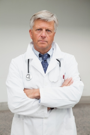 eye doctor: Serious doctor with folded arms in labcoat