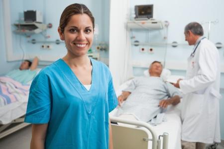 paciente: Enfermera de pie feliz en sala de hospital con el doctor y el paciente hablando en segundo plano