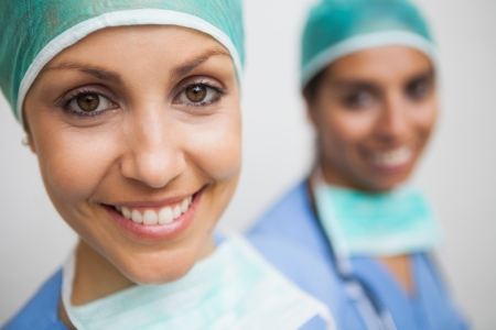 scrub cap: Smiling nurse in surgical cap with other smiling nurse in background Stock Photo