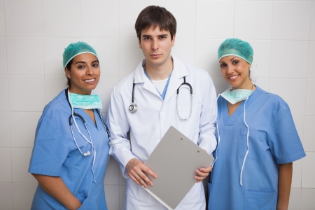 Doctor with clipboard stands between two smiling nurses photo