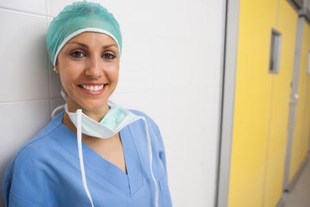 enfermera con cofia: Enfermera sonriente se inclina contra la pared blanca en el pasillo del hospital Foto de archivo