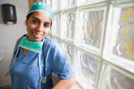 Happy nurse in scrubs leans glass wall in hospital  photo