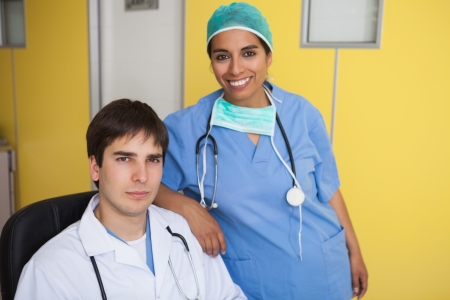 Happy doctor sitting in leather chair with nurse standing in yellow office photo