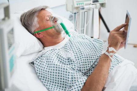 oxigeno: El paciente descansa en la cama leyendo lleva una m�scara oxegen en sala de hospital Foto de archivo