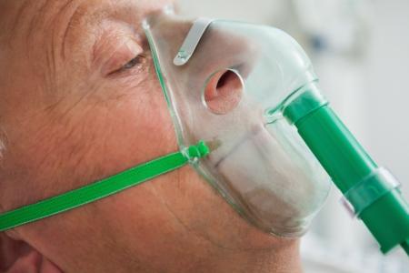 Man wearing oxegen mask in hospital photo