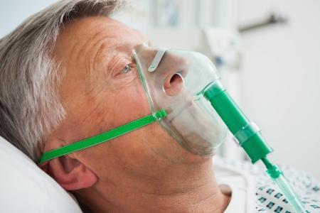 ox�geno: Hombre en la cama con m�scara de ox�geno en el hospital Foto de archivo