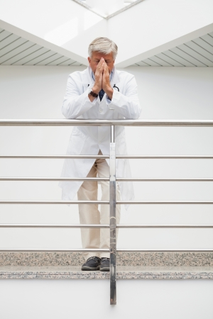 Worried doctor with face in hands leans against rail in hospital corridor photo