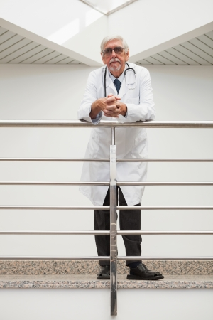 Doctor leaning on the railing with glasses with serious expression in hospital corridors photo