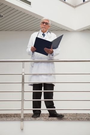 Doctor standing on the railing watching his papers photo
