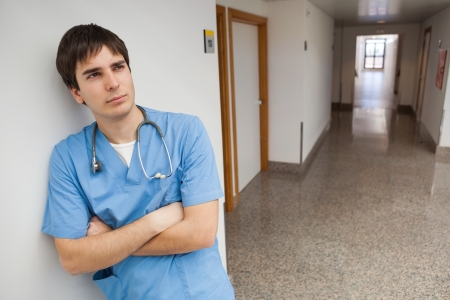 male nurse: Nurse is leaning on the wall of the corridor in the hospital thinking