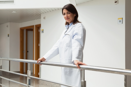 Doctor standing at the railing smiling in hospital corridor photo