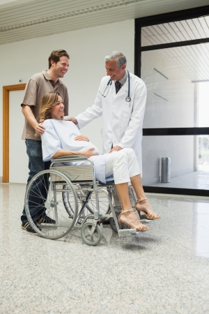 gynaecology: Doctor is talking to a pregnant patient in a wheelchair in the corridor of the hospital