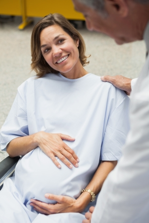 Smiling pregnant woman in wheelchair photo