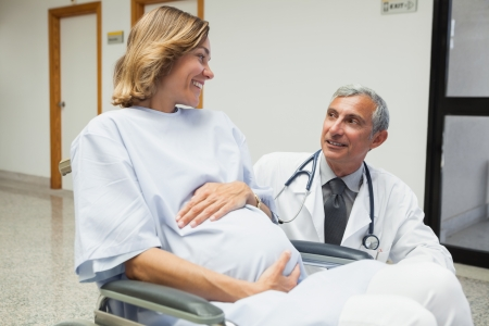 gynaecology: Doctor is talking to a pregnant woman in hospital corridor