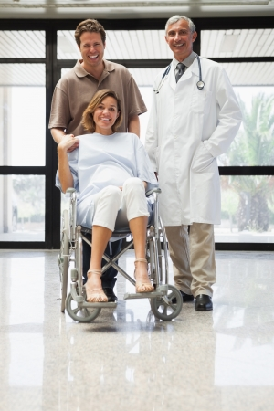 gynaecology: Pregnant woman in wheelchair, partner and doctor smiling in hospital corridor Stock Photo