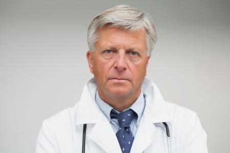 lab coat: Medico maturo che guarda serio camice indossa Archivio Fotografico