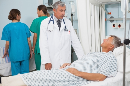 Patient lying in bed in hospital room talking to doctor photo
