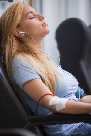 Woman donating blood and listening to music device in hospital Stock Photo - 15592755