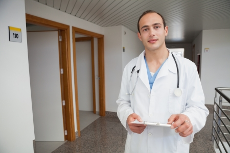 Smiling doctor in hallway holding a folder photo