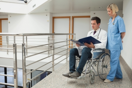 Doctor sitting in wheelchair examining notes with nurse in hospital corridor Stock Photo - 15592831