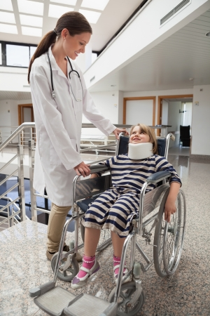 Female doctor smiling at child in wheelchair and neck brace in hospital corridor photo