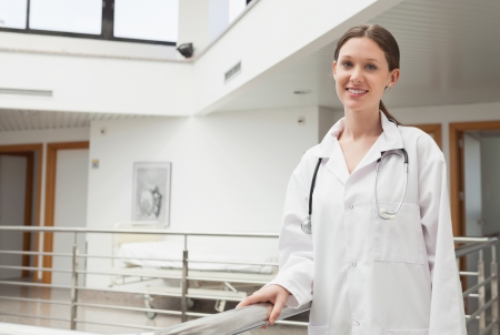 Female doctor leaning on the railing in hospital stairwell photo
