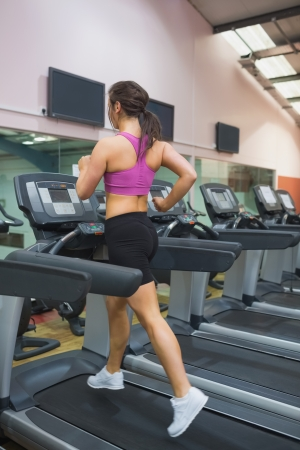 Woman running and training on a treadmill in a gym wearing black shorts and purple top photo