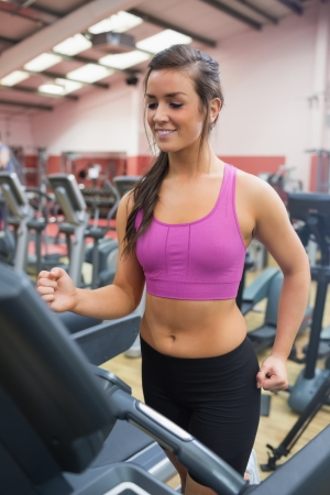 front facing: Woman running and training on a treadmill in a gym wearing black shorts and purple top happy front facing Stock Photo