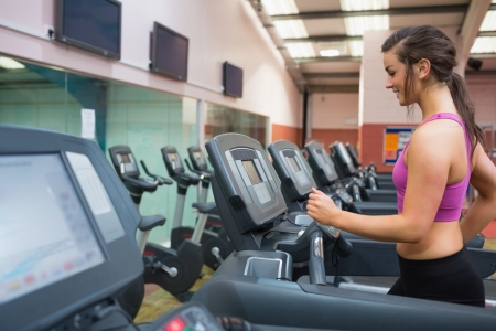 Woman running and training on a treadmill in a gym wearing black shorts and purple top Stock Photo - 15592609