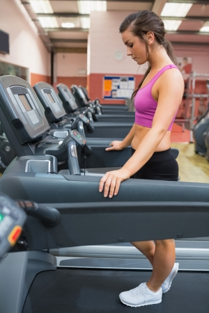 Woman taking a rest on the treadmill after exercising in gym photo