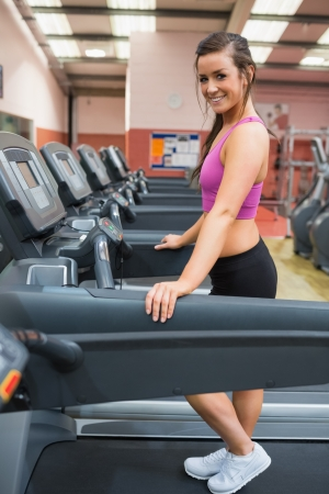 Woman taking a break on the treadmill after exercising photo