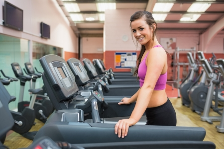 Smiling woman resting on a treadmill in the gym after jogging and running photo