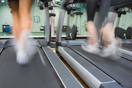 Two people running on treadmills in the gym photo