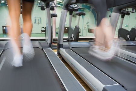 Two people running on treadmills side by side in the gym photo