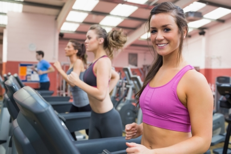 Smiling woman on a treadmill in the gym with other people photo