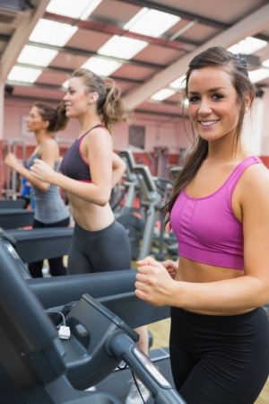 Happy women in the gym on treadmills photo