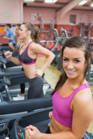 Women running on a treadmill in a gym smiling and exercising photo