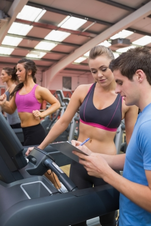 Gym Instructor helping woman in the gym on treadmill photo
