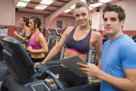Gym Instructor and woman in the gym on the treadmill photo