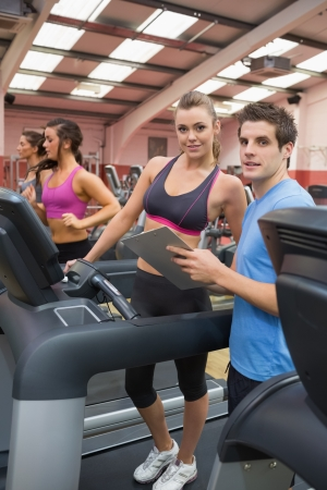 Gym Instructor and woman in the gym on the treadmill talking photo