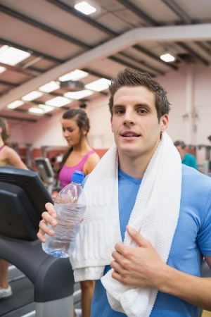 Man smiling and drinking a bottle of water in the gym