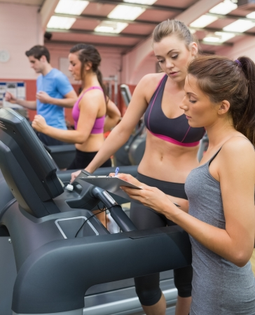 Female Instructor and woman in the gym on the treadmill photo