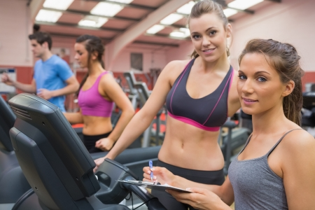 Smiling woman and instructor in the gym photo