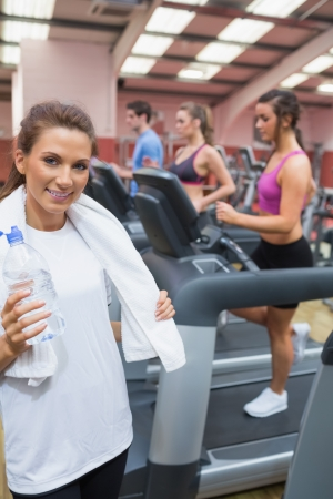 Woman smiling and drinking a bottle of water in the gym after exercise photo
