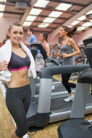 Woman smiling and drinking a bottle of water in the gym during exercise photo
