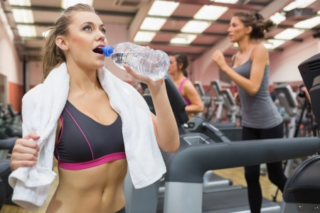 Woman drinking bottle of water in the gym during exercise photo
