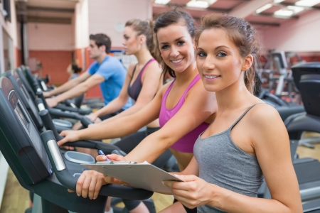 Gym Instructor and woman in the gym smiling on the exercise bicycle photo