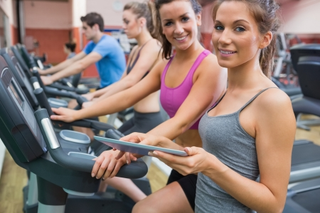 Instructor and woman smiling in the gym on the exercise bicycle photo