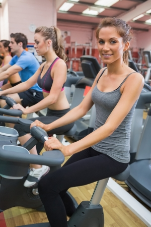 Woman smiling in the gym on exercise bicycle  photo