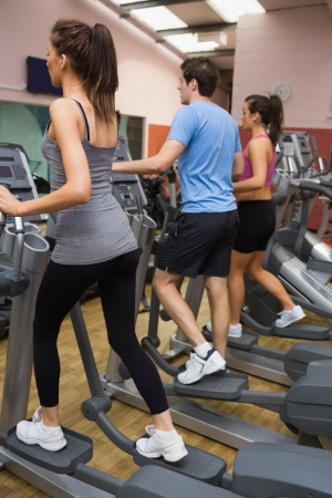 Three people training on  step machines in gym photo